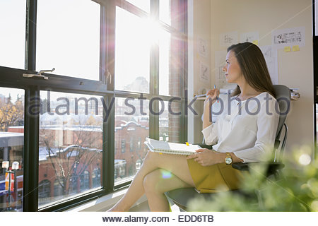 Pensive businesswoman looking out sunny office window - Stock Photo