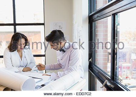 Architects discussing blueprints at office window - Stock Photo