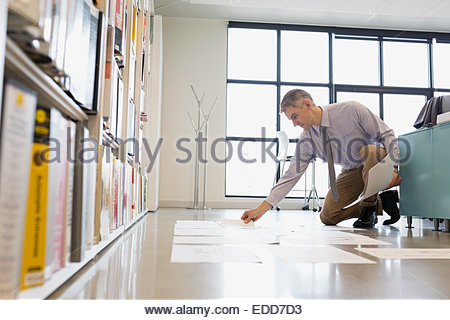 Architect laying plans out on floor - Stock Photo