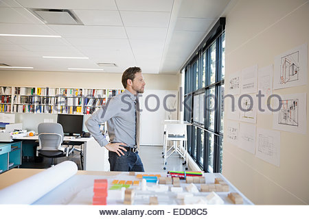Architect reviewing plans on wall - Stock Photo
