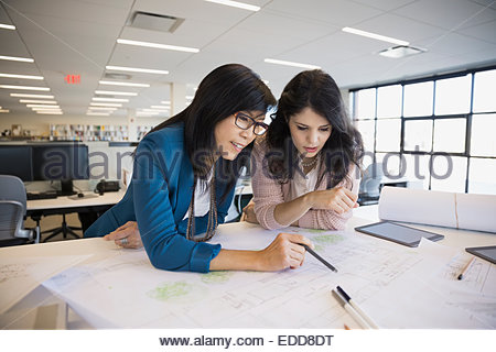 Architects drafting blueprints in office - Stock Photo