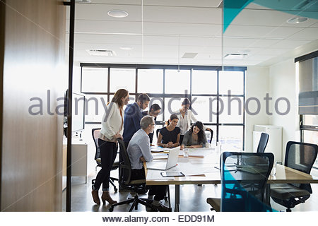 Business people huddled around conference table - Stock Photo