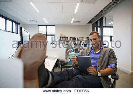 Businessman using digital tablet with feet up - Stock Photo