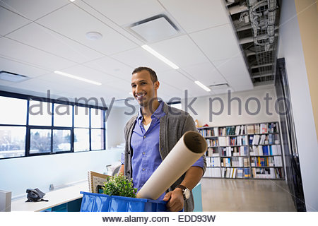 Portrait of smiling businessman carrying belongings in office - Stock Photo