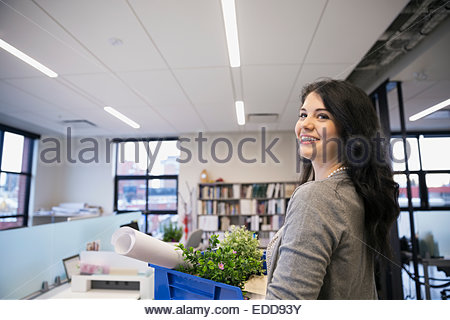 Portrait of smiling businesswoman carrying belongings in office - Stock Photo