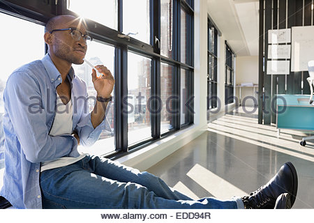 Pensive businessman at window in office - Stock Photo
