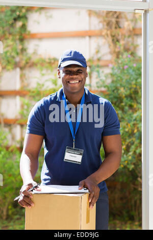 handsome African American delivery man with a parcel standing at the door - Stock Photo