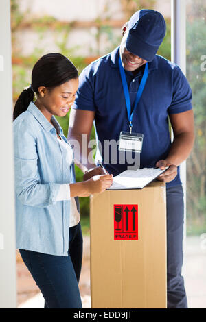 beautiful customer signing for delivery from courier - Stock Photo
