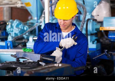 skilled factory mechanic using spanner fasten gumboot making machine - Stock Photo