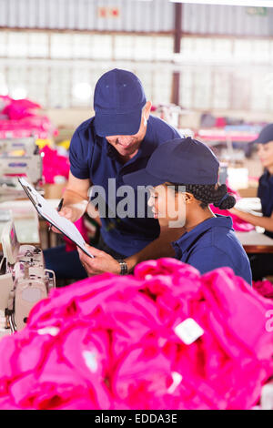 foreman and dressmaker looking at clipboard in factory - Stock Photo