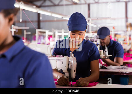 African textile factory machinist working in production line - Stock Photo