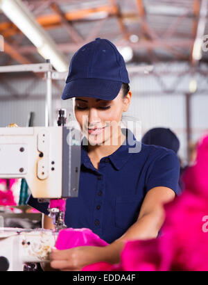 pretty female factory worker sewing garment - Stock Photo