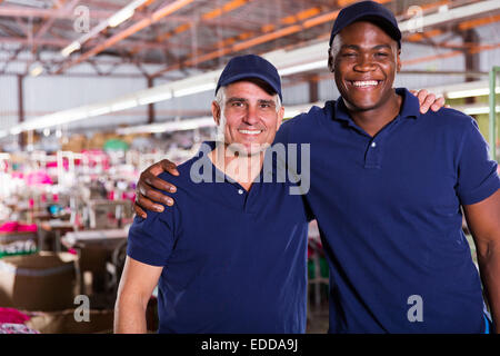 textile co-workers looking at the camera in factory - Stock Photo
