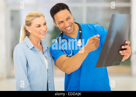 friendly medical doctor showing patient test results of x-ray - Stock Photo