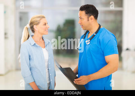 handsome mid age doctor discussing x-ray results to patient - Stock Photo
