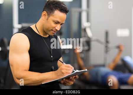 muscular mid age male gym trainer writing on clipboard - Stock Photo