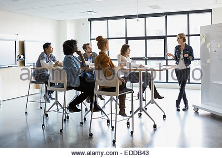 Businesswoman at whiteboard leading meeting in conference room - Stock Photo