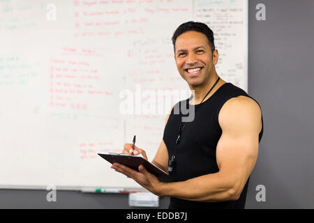 professional middle aged male trainer writing on clipboard - Stock Photo