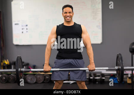 middle aged male bodybuilder exercising with a barbell - Stock Photo