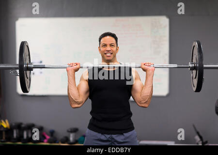 muscular man lifting weights in health club - Stock Photo