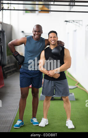 happy young African boxer with his trainer at gym - Stock Photo