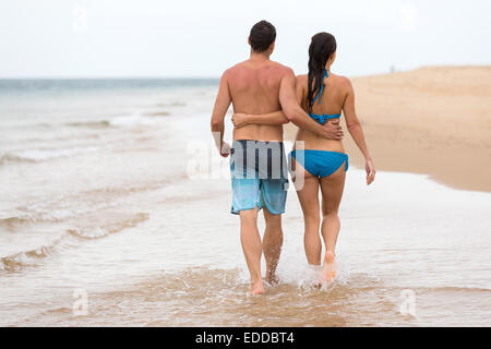 back view of couple walking on beach together - Stock Photo