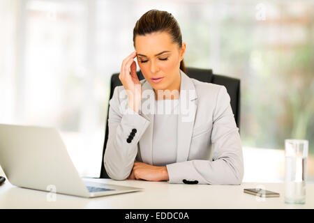 sad businesswoman sitting in modern office - Stock Photo