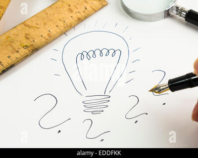 Drawn lightbulb and question marks on white paper - Stock Photo