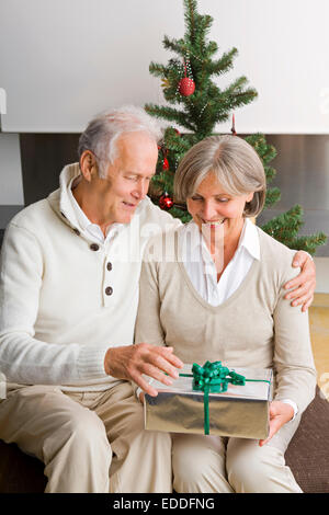 Senior couple exchanging Christmas presents at home - Stock Photo