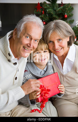 Happy little boy receiving Christmas present from his grandparents - Stock Photo