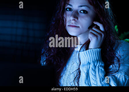 Woman Working with a Computer with Headset at Night - Stock Photo