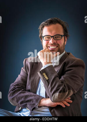 Portrait of smiling man with full beard wearing glasses in front of dark background - Stock Photo