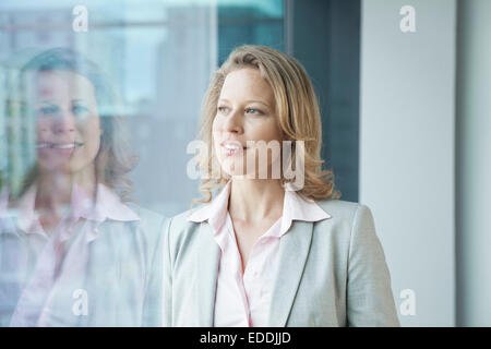 Businesswoman in office looking out of window - Stock Photo