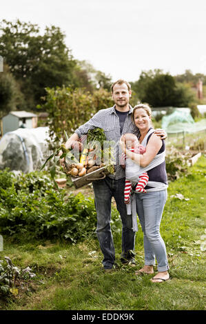 Young family standing in their allotment, smiling. Man holding a box full of freshly picked vegetables. - Stock Photo