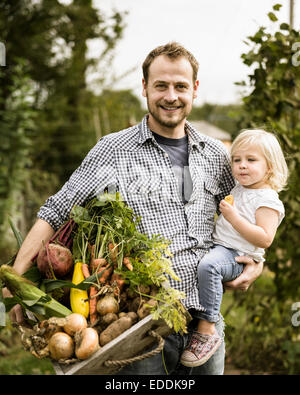 Man standing in his allotment with his daughter, smiling, holding a box full of freshly picked vegetables. - Stock Photo