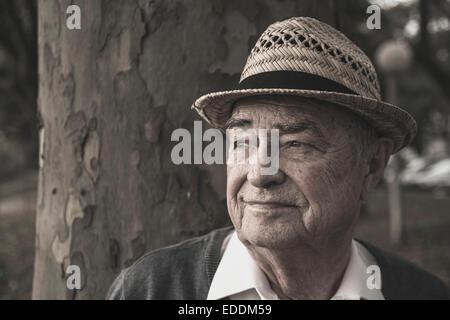 Senior man wearing straw hat thinking - Stock Photo