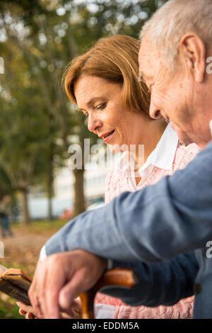 Daughter reading to senior man outdoors - Stock Photo