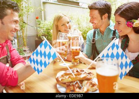 Happy friends in bavarian beer garden drinking beer in summer - Stock Photo