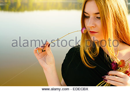 unusual gothic girl with long red hair and dried-up flowers near lake - Stock Photo
