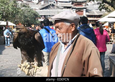 Golden eagle and local handler, Si Fang Jie (town square), Lijiang, Yunnan, China - Stock Photo
