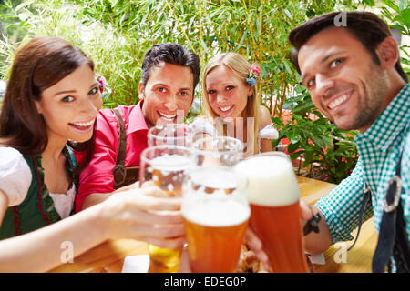 Smiling friends in beer garden clinking their glasses in summer - Stock Photo