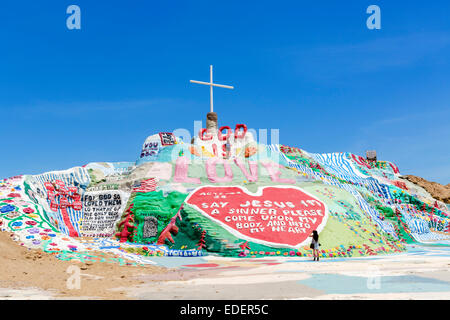 Tourist posing on Salvation Mountain, Leonard Knight's large scale piece of religious folk art, Niland, California, - Stock Photo