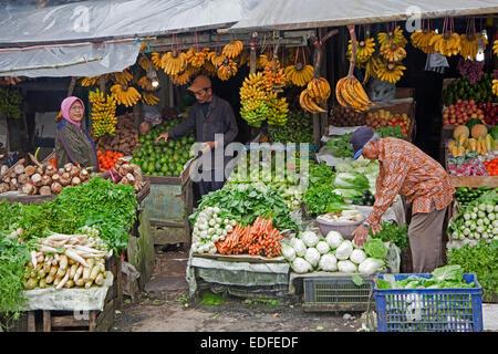Indonesian vendor selling fruit and vegetables on display at grocery shop, Bogor Regency / Kabupaten Bogor, Java, - Stock Photo