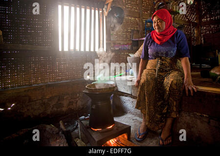 Indonesian elderly, woman cooking rice in traditional bamboo house, Cianjur Regency, West Java, Indonesia - Stock Photo