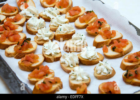 Delicious appetizer canapes with bread, salmon and cheese cream. Selective Focus - Stock Photo