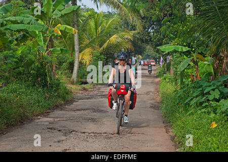 Western tourist cycling along rural country road in the Cianjur Regency, West Java, Indonesia - Stock Photo