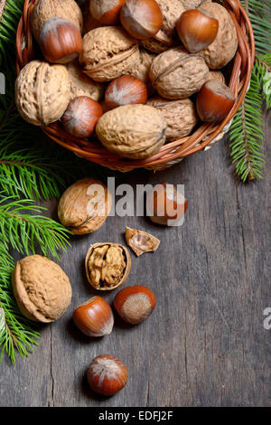 Walnuts and hazelnuts in  bowl isolated on old wooden background - Stock Photo