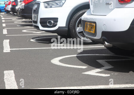 Cars parked in a row of disabled parking spaces - Stock Photo