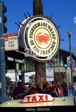 Sign at busy entrance to the Fisherman's Wharf with Taxi sign in foreground Embarcadero San Francisco California - Stock Photo
