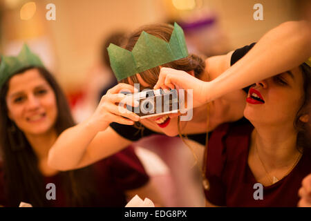 A young adult woman guest wearing a green paper hat crown  at a wedding reception or Christmas party leaning forward - Stock Photo